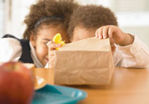 kids looking in brown bag lunch