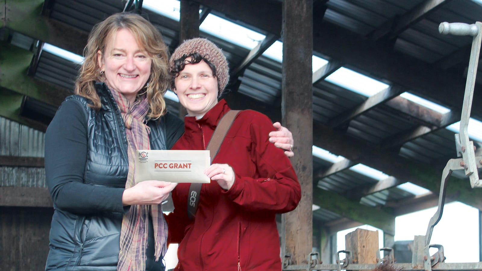 Green Lake Village PCC store director Celeste Coxen gives Jennifer McKeown a PCC Grant.