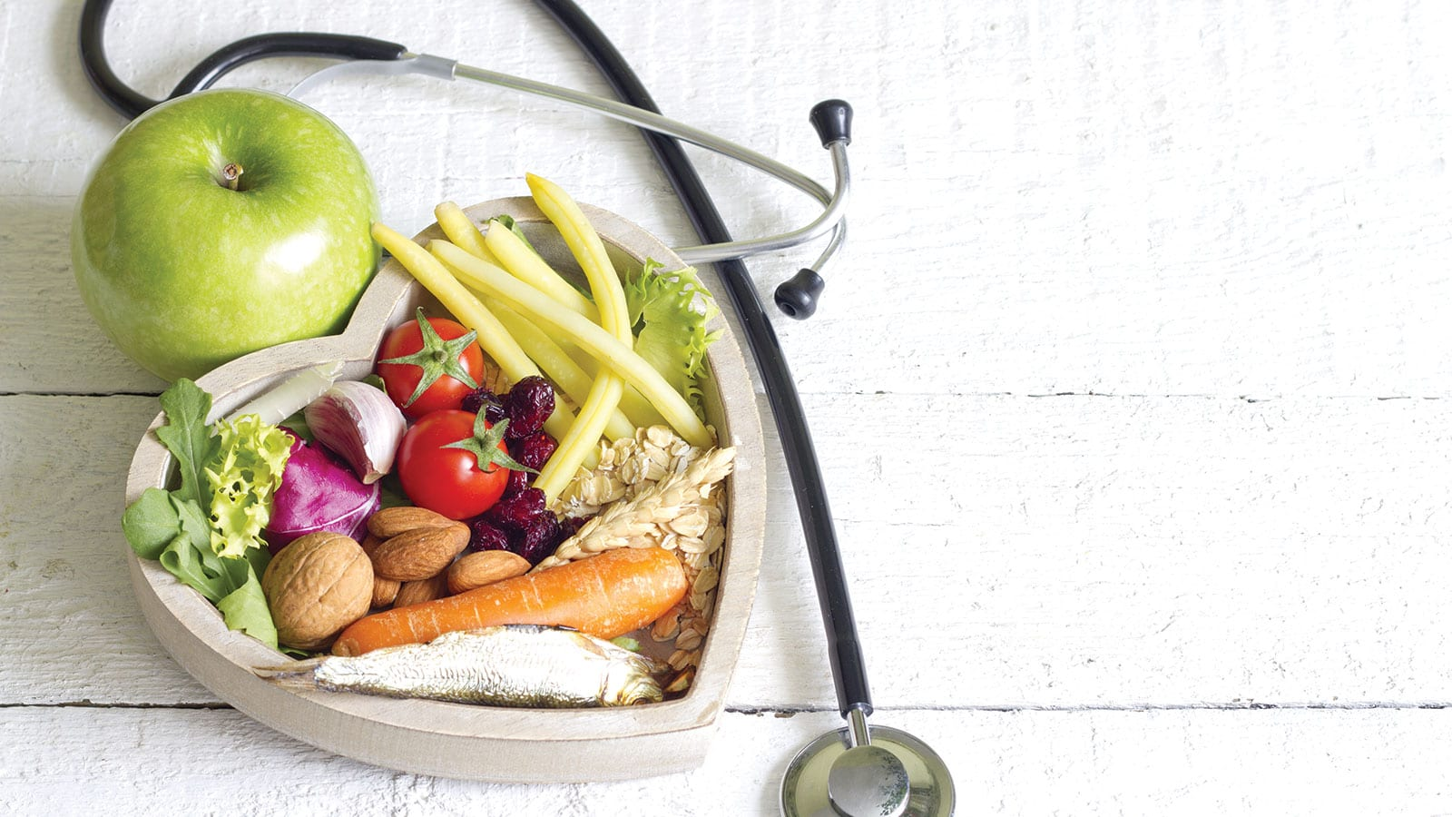 Nutritious fresh foods and seafood in a heart-shaped wood container surrounded by a stethiscope.