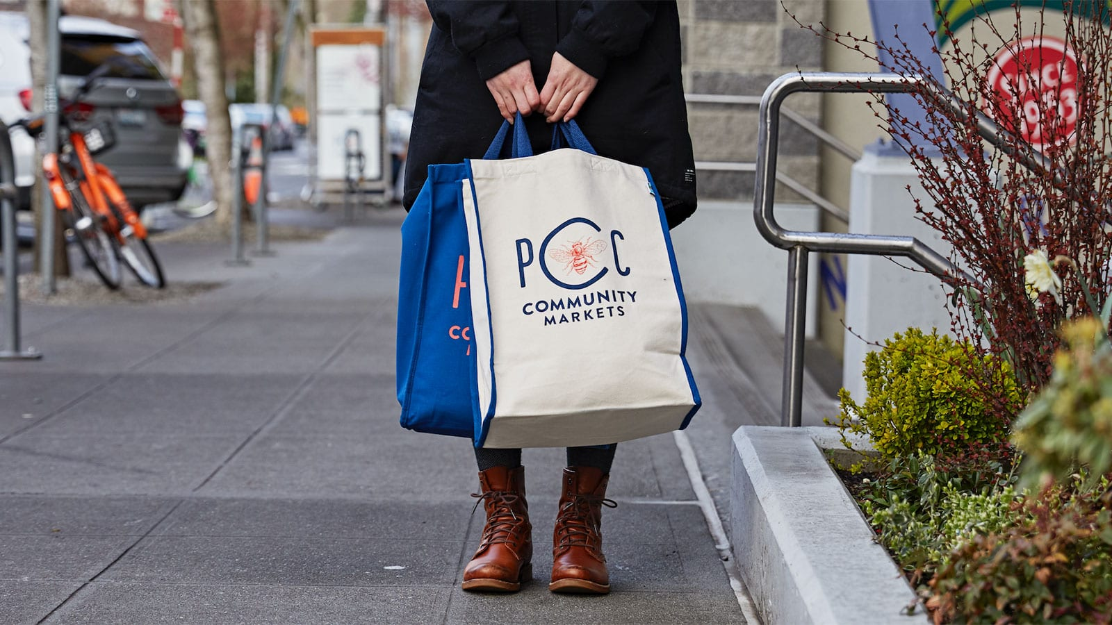 PCC member holding PCC branded totes outside of Fremont PCC.