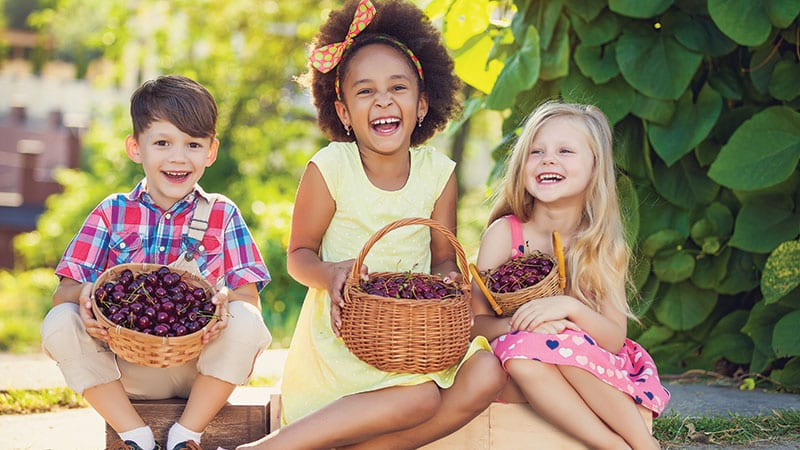Cute children holding baskets of cherries.