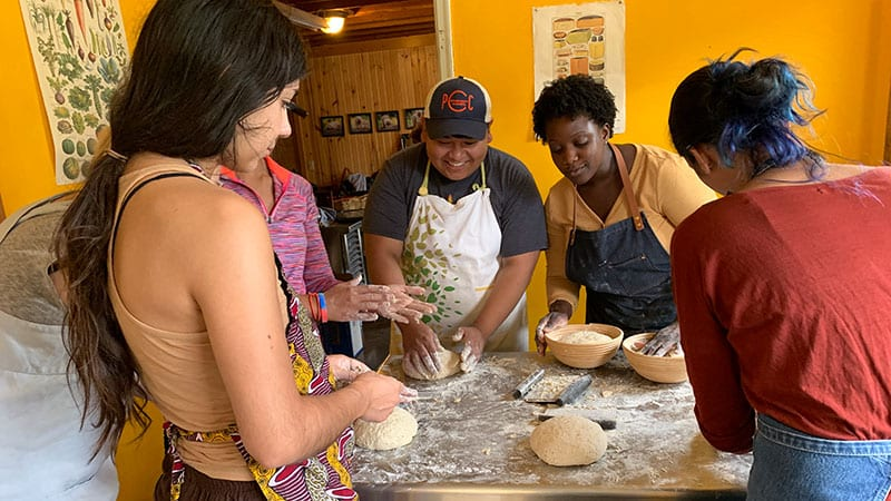 Arvin Batingan, Daela Muñoz and Chef Natalie Evans baking at an event at Quillisicut Farm.
