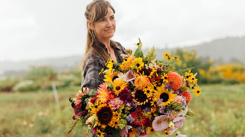 Young farmer holding an enormous bouquet of harvested flowers at Sweet Alyssum Farm. Photo by Rylea Foehl courtesy of Pierce County Fresh.