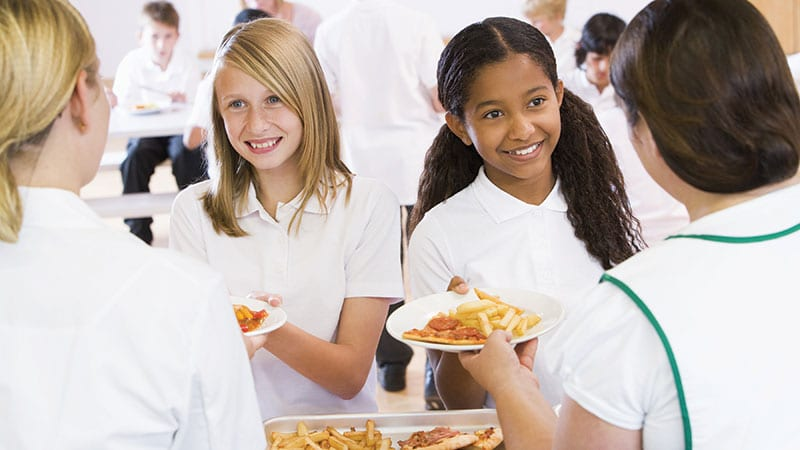 Kids in cafeteria receiving unhealthy lunch
