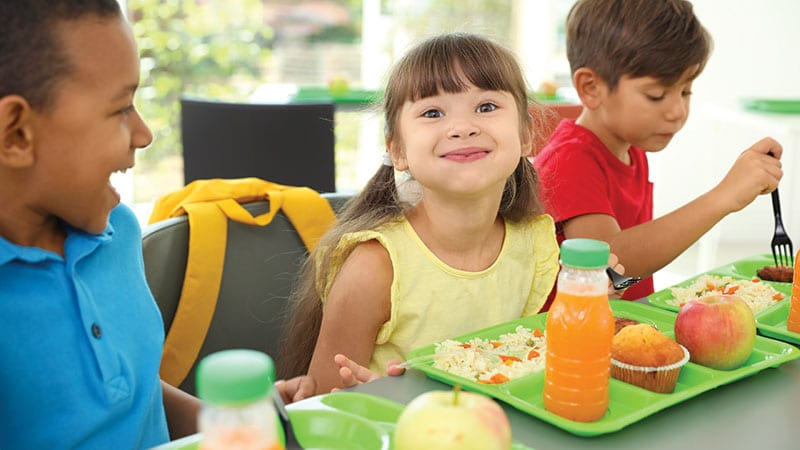 Young children eating healthy school lunch